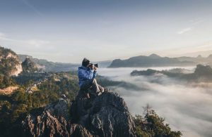 Photographer using gadgets while traveling